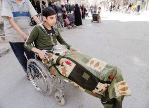 A boy sitting in a wheelchair waits for food to be distributed in the besieged al-Yarmouk camp, south of Damascus